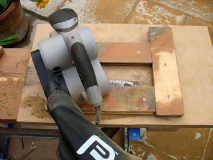 As I'm not removing radiators in the kitchen, I'd quite like my border blocks to be half-finished, or I'll never be able to sand them down as they are, once they're cut around rad pipes. I set up a simple jig outside to hold individual blocks, by screwing three waste blocks to a board.