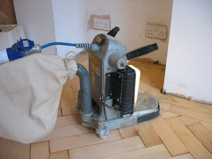 To get into the edges where the big sander won't reach, you need an edger. This is a heavyweight orbital sander. Go through the grits at the same pace as the sander, i.e, main floor with 25 grit, then edging with 25 grit, and so on.